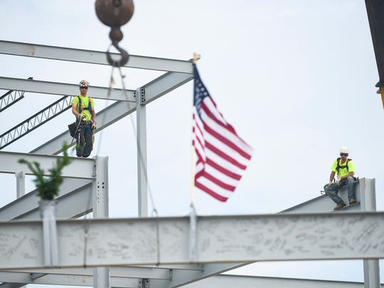 Construction workers wait patiently as a beam that's