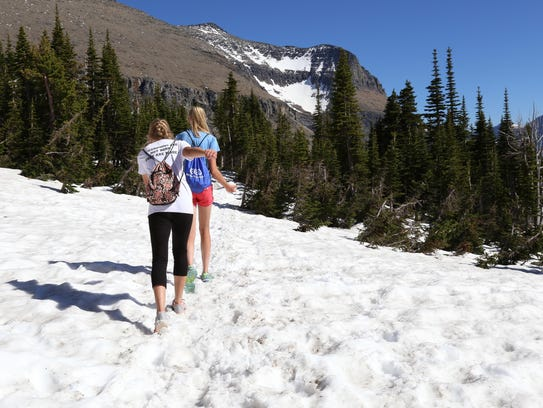 Lizzie, front, and Hallie Thompson walk in a snow field