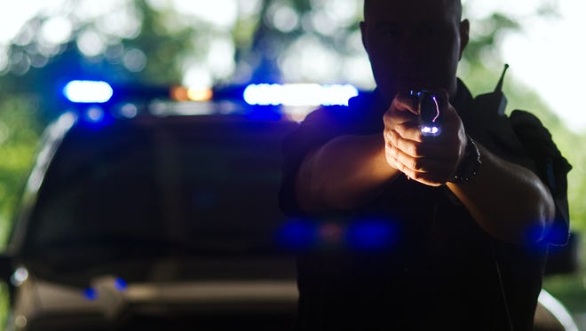 During a test in 2009, a police officer pulls the trigger on a TASER X26 Electronic Control Device, with the capability of shooting 2 small probes about 10 yards, transmitting electrical pulses through the wires and into the body, debilitating the person's sensory and motor functions.