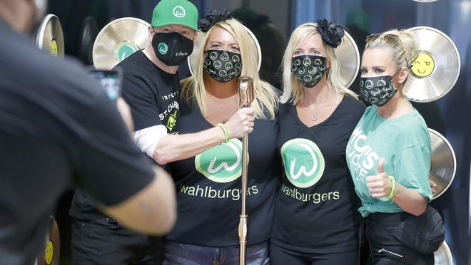 Chrissie Butkus, center right, and Michelle Greybill, center left, both of New Lenox, get their picture taken with Donnie Wahlberg and Jenny McCarthy during Wahlburgers restaurant opening day Tuesday, July 28, 2020, in St. Charles.
