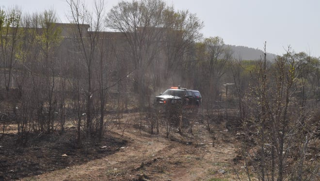 Local fire crews mop up after a grass fire along the river in Ruidoso Downs Tuesday.