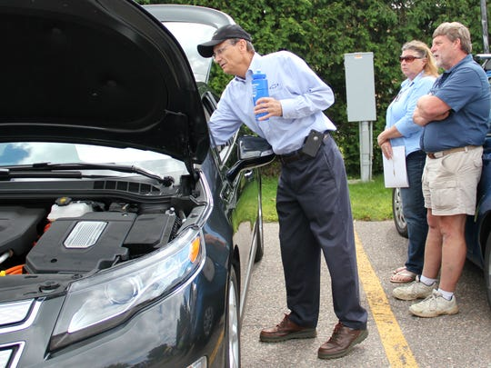 David Bokan, left, of Shearer Automotive in South Burlington, shows an electric car to Sandy Riggen and Rich Williams of Jeffersonville at the SUN CARnival in 2014.