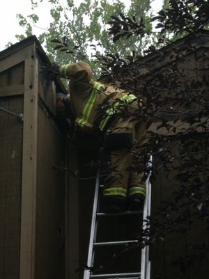 A Richmond firefighter peers into the attic of a Walnut Lane home Tuesday morning to ensure a fire has been extinguished.