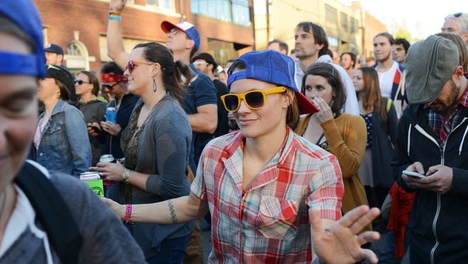 Mary Beth Selzler of Asheville, center, dances with her friends at Mix Master Mike's show during Moogfest 2014.
