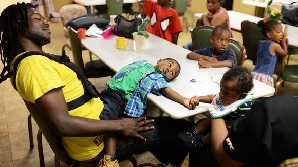 Lavarion Bailey, 2, sits on his father lap and holds hands with his brother, Lavar II, on a typical morning at the Western Carolina Rescue Mission. Families have to be out of their rooms by 6:30am and often have nowhere to go so they wait in the dining area. 6/16/14