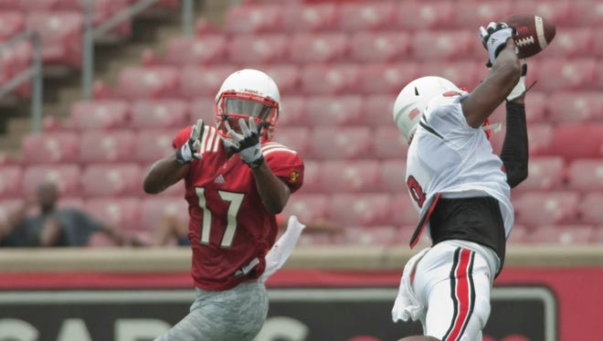 UofL safety Gerod Holliman intercepts a ball intended for UofL wide receiver James Quick during a team scrimmage at Papa John's Cardinal Stadium. 09 August 2014