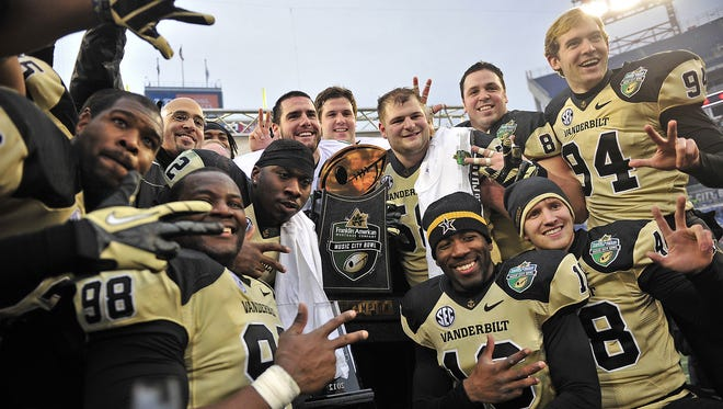 Vanderbilt head coach James Franklin and players ;pose for a photograph with the trophy after defeating North Carolina State 38-24 during the Music City Bowl at LP Field in Nashville, Tenn., Monday, Dec. 31, 2012.
