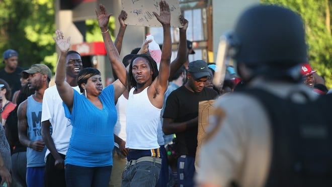 A crowd protests the killing of teenager Michael Brown on Tuesday in Ferguson, Mo. Brown was shot and killed by a police officer on Saturday in the St. Louis suburb.