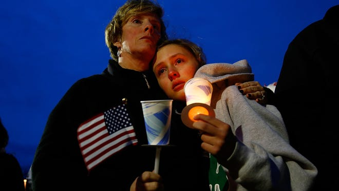 A mom and daughter attend a vigil April 16, 2013, for Martin Richard, 8, who was killed by the blast near the finish line of last year's Boston Marathon.