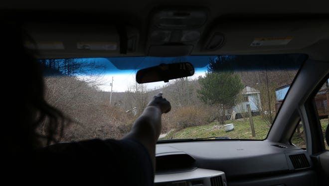 Pharmacy technician Kasey Adkins points out the home of a patient to a colleague while delivering prescriptions to patients in Floyd County, Ky. The remoteness of the region makes it difficult for patients to access their medicines, so sometimes clinic staff bring them to patients' homes. Mar. 19, 2014. [Via MerlinFTP Drop]