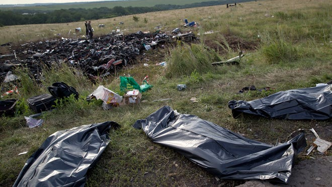 Bodies of victims are covered in plastic sacks at the crash site of Malaysia Airlines Flight MH17 near the village of Hrabove, eastern Ukraine, July 19, 2014.