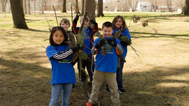 Mead Elementary Charter School second-graders pick up sticks and debris on April 21 at the Wisconsin Rapids Municipal Zoo.