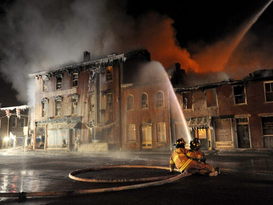 Firefighters battle a blaze on Jan. 6, 2014 at the Emmitt House in Waverly in this photo that's a finalist in the Best News Photo category of the Ohio Associated Press Managing Editors Better Newspaper Contest for work published in 2014.