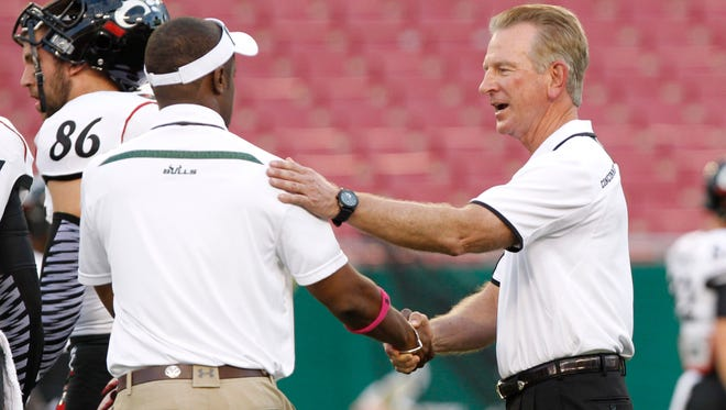 Bearcats head coach Tommy Tuberville talks with Bulls head coach Willie Taggart prior to their game at Raymond James Stadium in October of 2013.