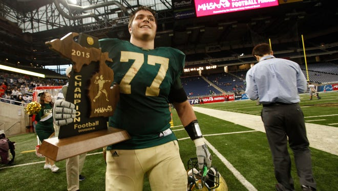 Muskegon Catholic Central 's Jacob Holt carries the trophy after a 7-0 victory over Waterford Our Lady of the Lakes in the MHSAA Division 8 state football championship at Ford Field in Detroit on Friday, Nov. 27, 2015.