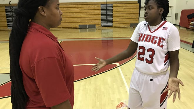 Seminole Ridge junior guard/forward Jahnae Midget, right, talks to Hawks coach Maria Hudson after a recent win over Park Vista in Loxahatchee. Midget is a Division I college prospect and has drawn interest from North Florida, among others.
