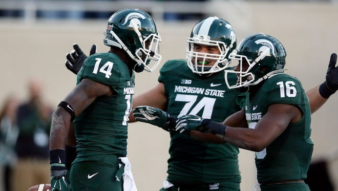 Michigan State receiver Tony Lippett (14) is congratulated by offensive tackle Jack Conklin (74) and wide receiver Aaron Burbridge (16) after a touchdown against Michigan on Oct. 25, 2014. Lippett was drafted by the Miami Dolphins and will be converted to cornerback, while Conklin could be a first-round pick in the 2016 draft.