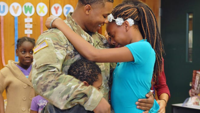 Army Specialist Anthony Foster made a surprise visit to his siblings at Oak Park elementary school.  Hugging him is Jerry and Alaysia.They did not know that he would be home on leave for the holidays. Foster is in the 3rd Brigade in the 4th Infantry Division, and has not seen his siblings his almost a year.