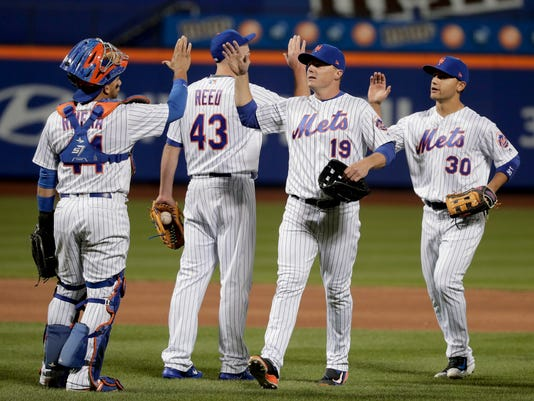 New York Mets' Jay Bruce (19) and Michael Conforto (30) high five catcher Rene Rivera (44) and pitcher Addison Reed (43) after the Mets beat the Miami Marlins 5-2 in a baseball game, Sunday, April 9, 2017, in New York. (AP Photo/Julie Jacobson)