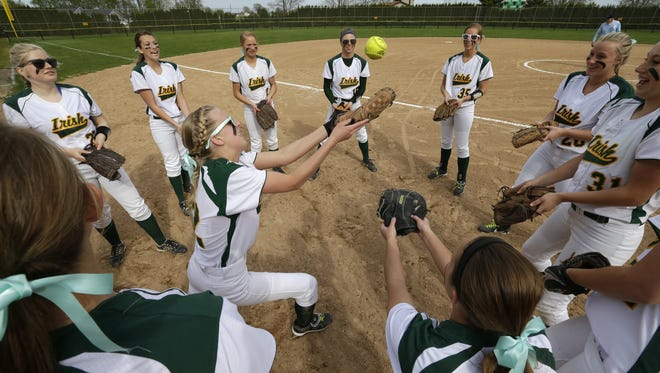 Freedom High School's softball players play a little hot potato before taking to the field against Little Chute High School Tuesday, May 5, 2015, in Freedom, Wis.