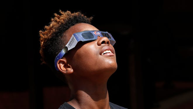 Jarquavious Ward tries out his solar eclipse glasses on Monday morning in Hopkinsville.  Aug. 21, 2017