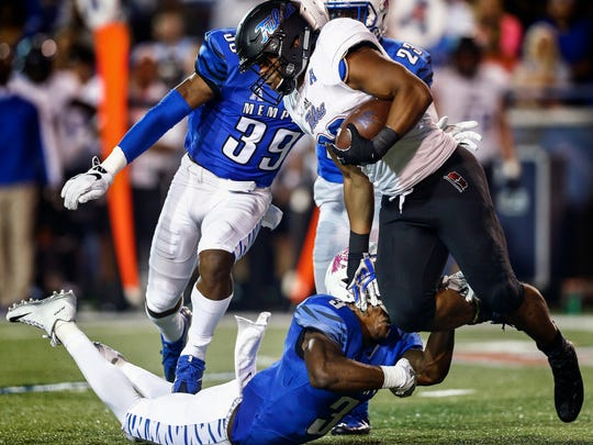 University of Memphis defender Anthony Miller (bottom) loose his helmet while bring down University of Tulsa kickoff returner Raymond Taylor (right) during second quarter action at the Liberty Bowl Memorial Stadium.