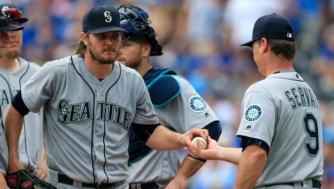 Seattle Mariners manager Scott Servais (9) takes the ball from starting pitcher Wade Miley, left, during the sixth inning of a baseball game against the Kansas City Royals at Kauffman Stadium in Kansas City, Mo., Saturday, July 9, 2016. (AP Photo/Orlin Wagner)