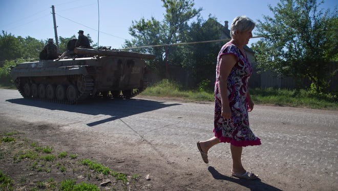 A woman passes Ukrainian servicemen as they ride on an armored military vehicle near Artemivsk, Ukraine, on June 9, 2015.