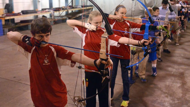 Christian Blair, (from left to right) Liz Vrana and Kelly Stalter take aim during Fairfield Christian Academy archery practice Wednesday in Lancaster.