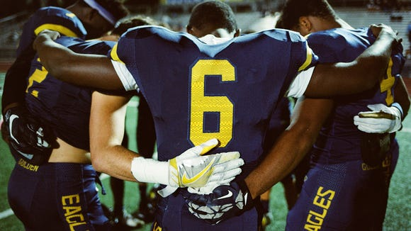 Naples defensive back Hervangelot Lordeus, center, and teammates come together for a group prayer before their game against the Largo Packers on Nov. 17, 2017.