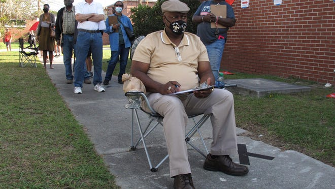 Savannah's Richard Williams sits in a folding chair, filling out paperwork, as he waits in line to vote.