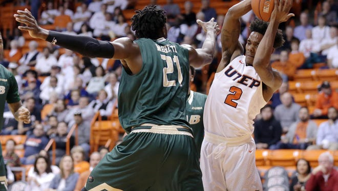 UTEP guard Omega Harris tries to avoid UAB's Tosin Mehinti as he drives to the basket Thursday night at the Don Haskins Center.