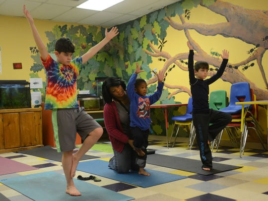 Jency Sterling (center, back) helps son Jonah Sterling, 4, with a tree pose while they and Sellers Forrest (left) and Bradley Wilson (right) take a yoga class at the Children's T.R.E.E. House Museum Saturday, Feb. 28, 2015. The class was instructed by Elizabeth Forrest of Vogue Yoga which is located in Pineville.