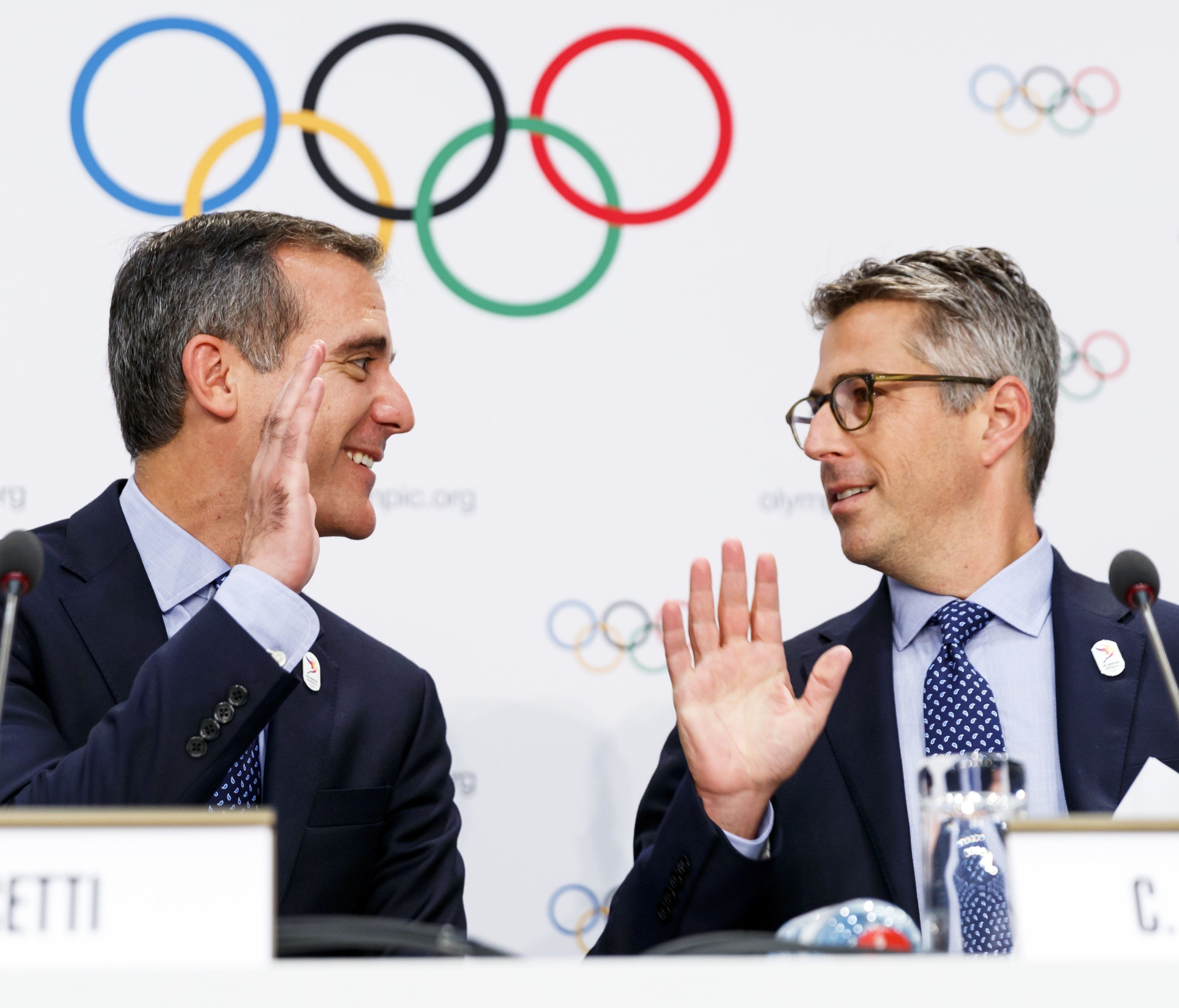 Eric Garcetti, mayor of Los Angeles, left, and Casey Wasserman, chairman of Los Angeles 2024, right, high five each other during a news conference after the presentation of Los Angeles 2024 Candidate City Briefing for International Olympic Committee