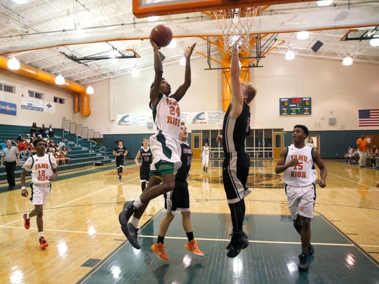 FAMU DRS' Dizavier Harris tries to lay the ball up over Christ's Church Academy's Caleb Gay during first-round playoff game.