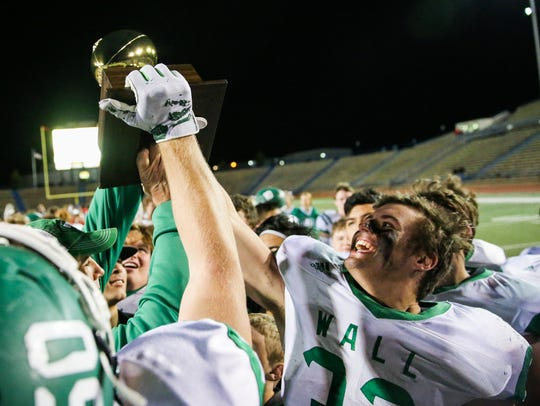 Wall senior captain and two-way player Tymber Carr (32) helps hoist the area-round trophy Friday, Nov, 24, 2017, after the Hawks beat Jim Ned, 52-21, in Class 3A Division I playoff action.