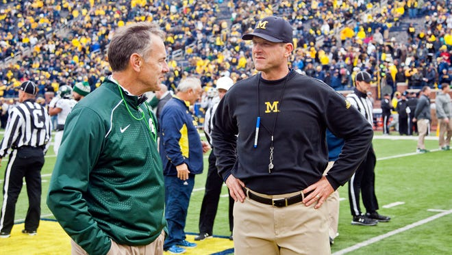Michigan State head coach Mark Dantonio shakes hands with Michigan head coach Jim Harbaugh on the Michigan Stadium field before an NCAA college football game in Ann Arbor, Saturday, Oct. 17, 2015.