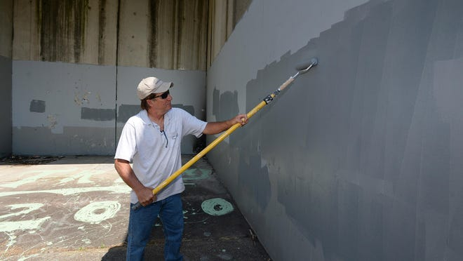 Chuck Robie, a construction mechanic with the city of Erie's Department of Public Works, paints over graffiti on the handball courts at Baldwin Park on Friday. The graffiti, which was racist in nature, covered parts of the handball and basketball courts and fencing.
