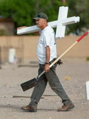 Samuel Holgun, with Knights of Columbus, joins with St. Genevieve Catholic Church Historical Society to install 49 crosses at San Jose Cemetery on Monday, May 28, 2018. The crosses were made by Stephen Elchlepp, with Tonto Basin Fort Reno VFW post 8807.