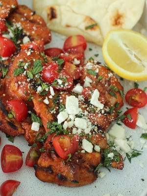 This July 13, 2015 photo shows grilled gochujang chicken thighs with feta and fresh mint in Concord, N.H. The gochujang has kick, but doesn't overwhelm, being both salty and savory with a touch of sweetness. (AP Photo/Matthew Mead)