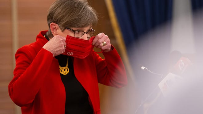 Gov. Laura Kelly puts on her mask following a news conference Wednesday at the Statehouse.