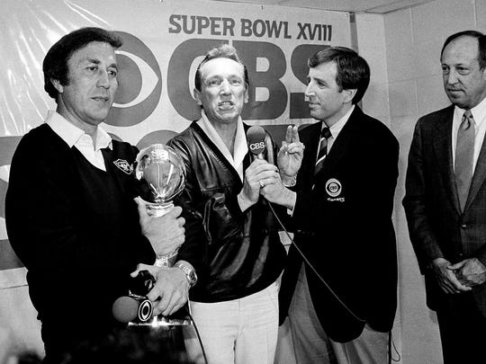 FILE - In this Jan. 23, 1984, file photo, Oakland Raiders coach Tom Flores clutches the Super Bowl trophy as Raiders managing general partner Al Davis is interviewed by Brent Musburger in the locker room after their 38-9 win over the Washington Redskins in Super Bowl XVIII in Tampa, Fla. At right is NFL Commissioner Pete Rozelle.