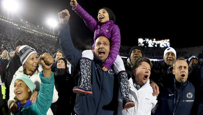 James Franklin says wife, Fumi (left, rear) and his daughters Shola (left, front) and Addy (on shoulders) have made him a better coach. He claims he better relates to and understands his players for having children of his own. Here, they celebrate after beating Michigan State to become Big Ten East champs.