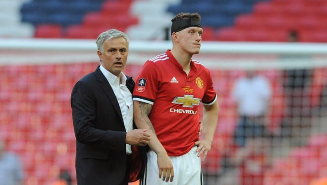 Manchester United manager Jose Mourinho, left, and Manchester United's Phil Jones on the pitch disappointed after losing the English FA Cup final soccer match between Chelsea v Manchester United at Wembley stadium in London, England, Saturday, May 19, 2018.