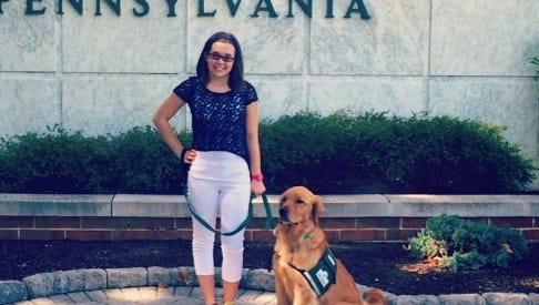 Blair Hagelgans is shown with her service dog, Creed, on the York College campus.