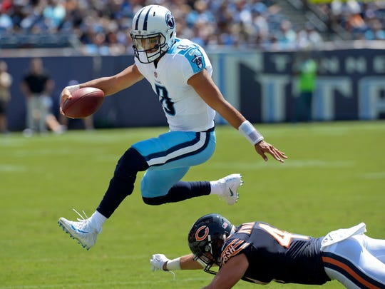 FILE - In this Aug. 27, 2017, file photo, Tennessee Titans quarterback Marcus Mariota (8) leaps over Chicago Bears inside linebacker Nick Kwiatkoski (44) in the first half of an NFL football preseason game, in Nashville, Tenn. As much as the Titans start their offense with the run, quarterback Marcus Mariota now has a lot more options when it comes to throwing downfield. (AP Photo/Mark Zaleski, File)