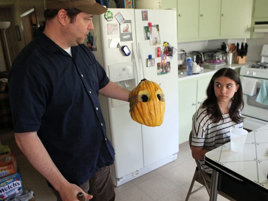 "Filmmaker Emily DiPrimio, 14 of Vineland, right, and her father Ron DiPrimio talk about her upcoming horror film ""Carver"" and examine the mask that will be used in the film."