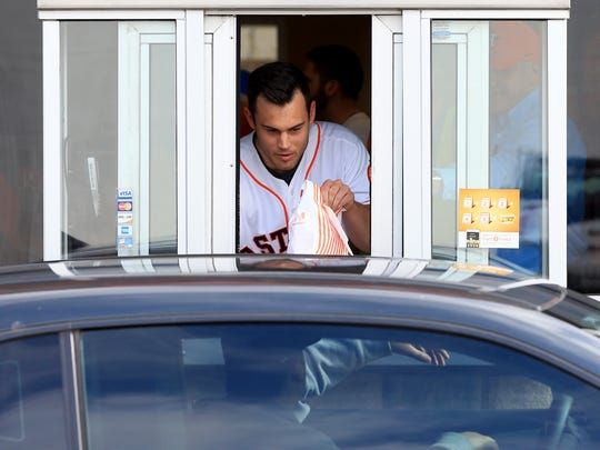 Houston Astros' Preston Tucker delivers a meal to a customer during the Houston Astros Caravan on Thursday, Jan. 19, 2017, at a Whataburger in Corpus Christi.