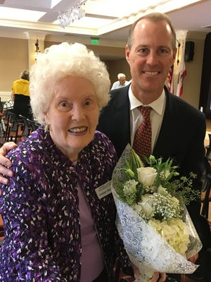 Warren Spieker, managing partner for Continuing Life, which provides business services for University Village Thousand Oaks, presents flowers to 10-year resident Evelyn Ballsun. Ballsun and Siri Eliason were the first residents to make a deposit to live at the retirement community a few years before it opened. University Village recently celebrated its 10th anniversary.
