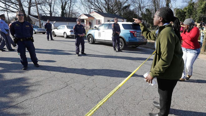 A woman yells at police near the scene of a fatal shooting in Raleigh, N.C., Monday, Feb. 29, 2016. Authorities say that a police officer shot and killed a man while trying to make an arrest for a felony drug charge. (AP Photo/Gerry Broome)